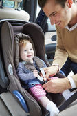 Father Putting Baby Into Car Seat — Stock Photo