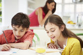 Children Doing Homework As Mother uses Laptop In Background — Stock Photo