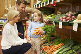 Family Choosing Fresh Vegetables In Farm Shop — Stock Photo