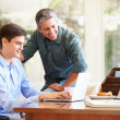 Father And Teenage Son Looking At Laptop — Stock Photo #50696721