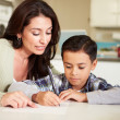 Hispanic Mother Helping Son With Homework At Table — Stock Photo #50697185