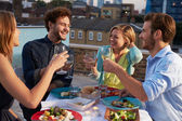 Group Of Friends Eating Meal On Rooftop Terrace — Stock fotografie
