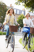 Two Women Cycling Through  Park — Stockfoto
