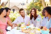 Freunde genießen mahlzeit auf outdoor party — Stockfoto