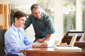 Father And Teenage Son Looking At Laptop — Stockfoto