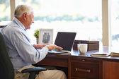 Starší muž pomocí přenosného počítače — Stock fotografie