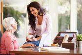 Tochter helfende mutter mit laptop — Stockfoto