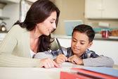Spansktalande mamma att hjälpa sonen med läxor vid bord — Stockfoto