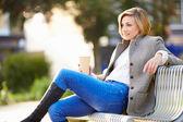 Kvinna avkopplande på parkbänk — Stockfoto
