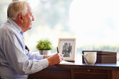 Senior Man Writing Memoirs In Book — Stock Photo