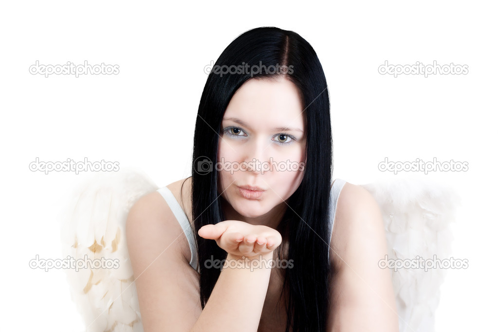 Young blackhaired woman with angel wings blowing some stars on white background  Stock Photo #14524455