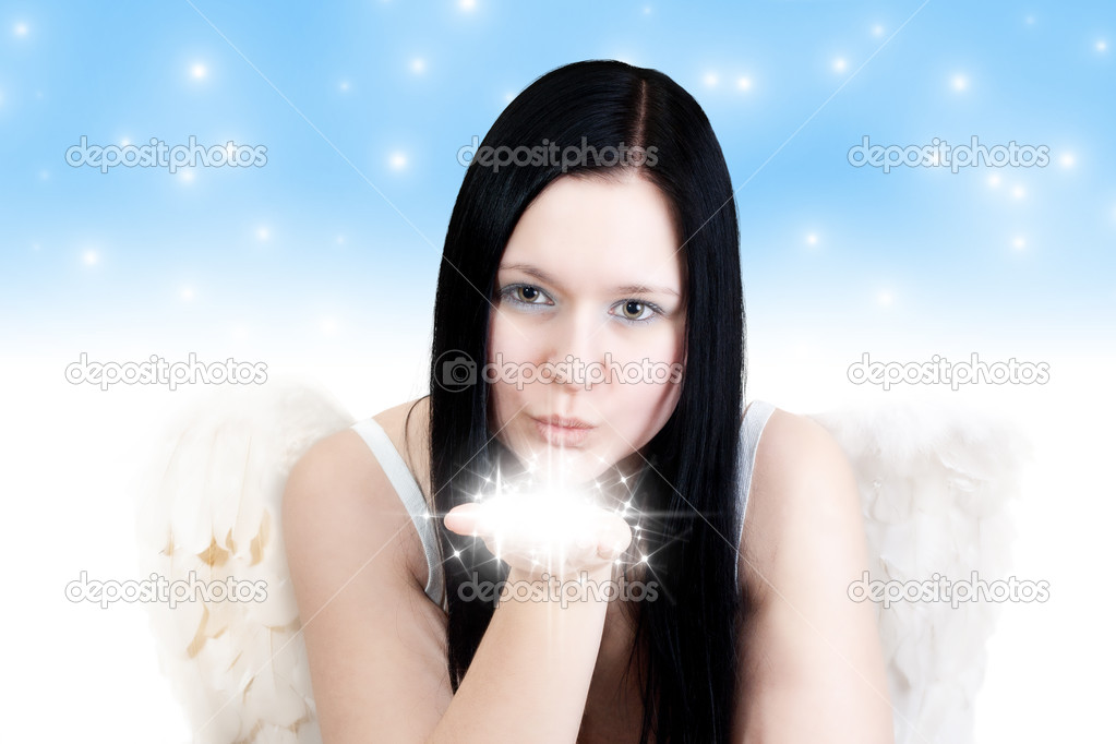 Young blackhaired woman with angel wings blowing some stars on blue background — Stock Photo #14524461