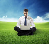 Business man with notebook sitting on grass — Stock Photo