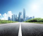 Droga asfaltowa i nowoczesne miasto — Zdjęcie stockowe