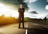 Business man on the road in sunset time — Stock Photo