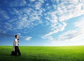 Young business man wolking at the field of grass — Stock Photo