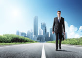 Business man walking on the road — Stock Photo