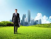 Homem de negócios, andando no campo verde e a cidade moderna — Fotografia Stock