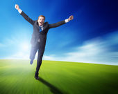 Happy business man running on blured spring field — Stock Photo