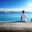 Young man relax siting on pier — Stock Photo #32712469