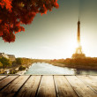 Wooden deck table and Eiffel tower in autumn — Stock Photo