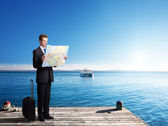 Business man standing on pier with map in hands — Stock Photo