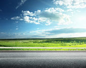 Asphalt road and perfect green field — Stock Photo