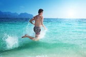 Running man in water of tropical sea — Stock Photo