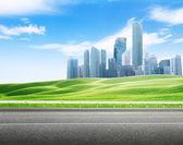 Asphalt road and modern city — Zdjęcie stockowe