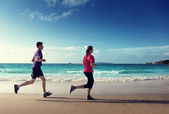 Man and women running on tropical beach at sunset  — Stock Photo