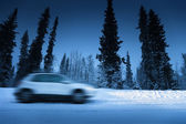 Lights of car and winter road in forest — Foto Stock
