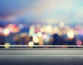 Asphalt road and blurred modern city — Stock Photo