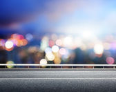 Asphalt road and blurred modern city — Stock Photo