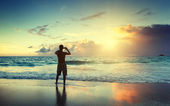 Young man on the beach take photo on mobile phone — Stock Photo