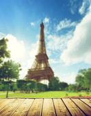 Eiffel tower in Paris and wooden surface — Stock Photo