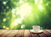 Cup coffee and sunny trees background — Stock Photo