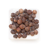 Black pepper (Piper nigrum) in a white bowl on white background. — Stock Photo