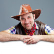Cheerful cowboy holding a banner — Stock Photo