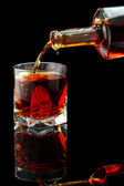Whiskey glass and bottle on a black — Stock Photo