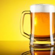 Glass of beer close-up with froth over yellow background — Stock Photo #27974963