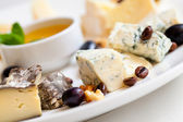 Still-life cheese platter with nuts and grapes — Stock Photo