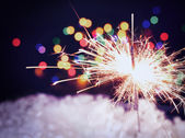 Holiday background with a beautiful sparkler — Stock Photo
