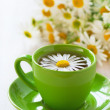 Herbal chamomile tea in a green cup — Stock Photo