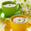 Herbal chamomile tea in a yellow cup - Stock Photo
