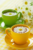 Herbal chamomile tea in a yellow cup — Stock Photo