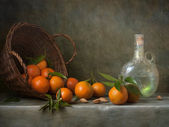 Still life with tangerines and antique bottle — Stock Photo