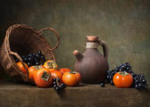Still life with persimmons and grapes — Stock Photo