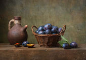 Still life with black plums in a basket — Stock Photo