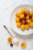 Apricots and cherries on a plate on a marble table — Stock Photo