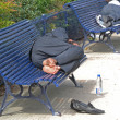Homeless sleeping on benches — Stock Photo